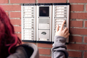 One person in the street presses a button on a intercom